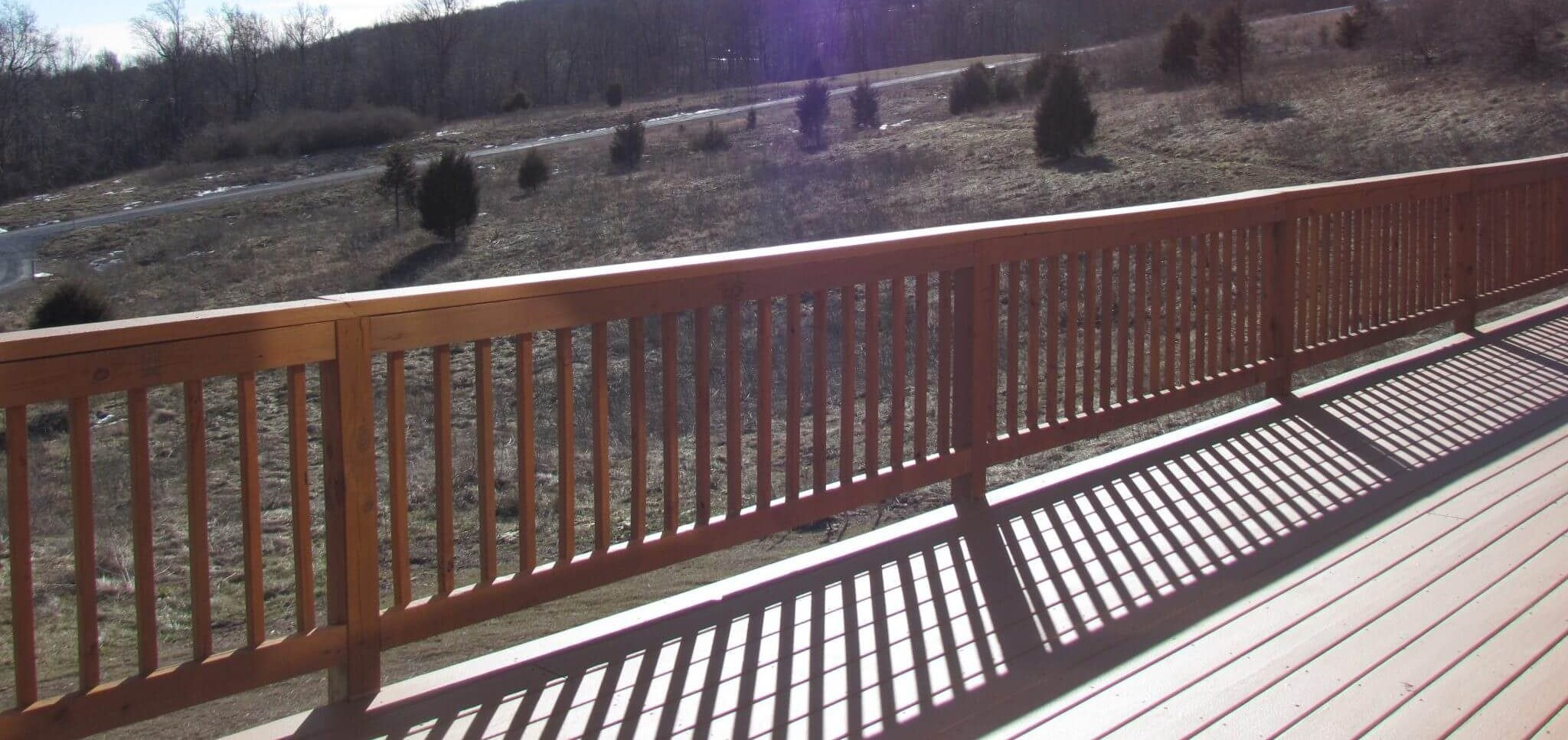 Cedar Siding Custom Home deck with bright sun